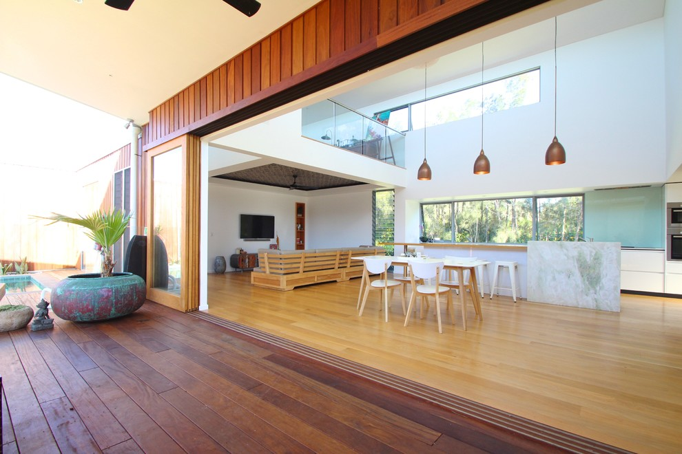 Inspiration for a large contemporary family room in Sydney with white walls, light hardwood floors and a wall-mounted tv.