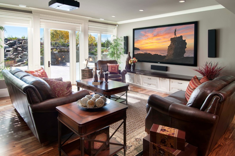 Mid-sized elegant medium tone wood floor family room photo in Calgary with gray walls and a wall-mounted tv