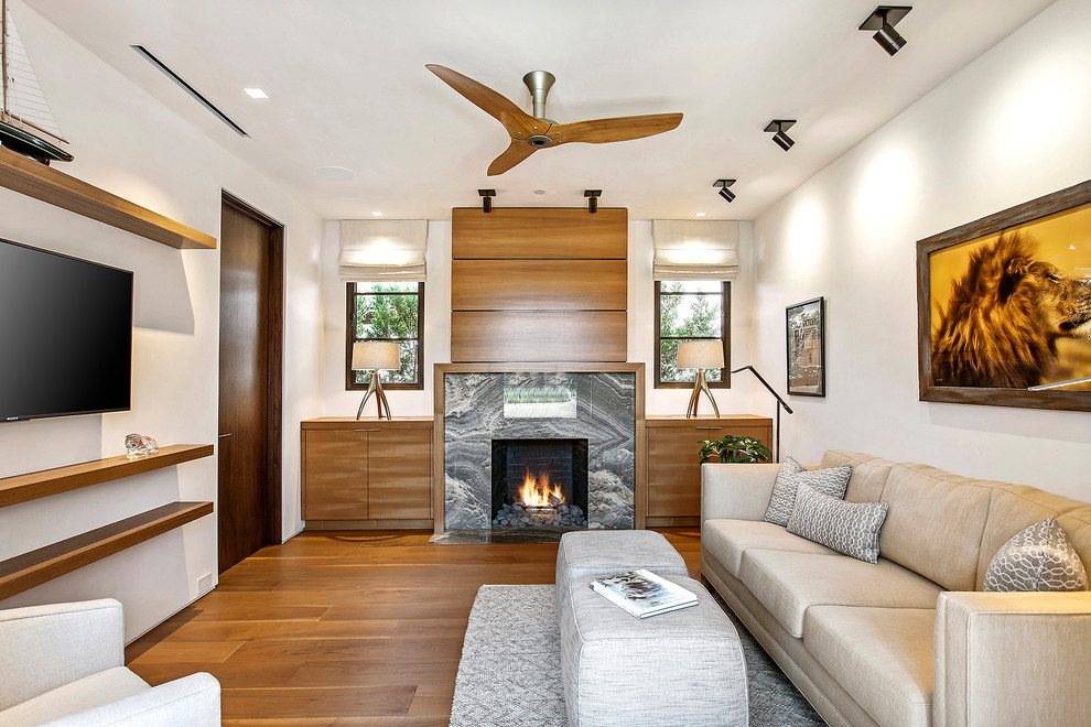 Example of a mid-sized trendy enclosed medium tone wood floor and brown floor family room design in Los Angeles with white walls, a standard fireplace, a wall-mounted tv and a stone fireplace