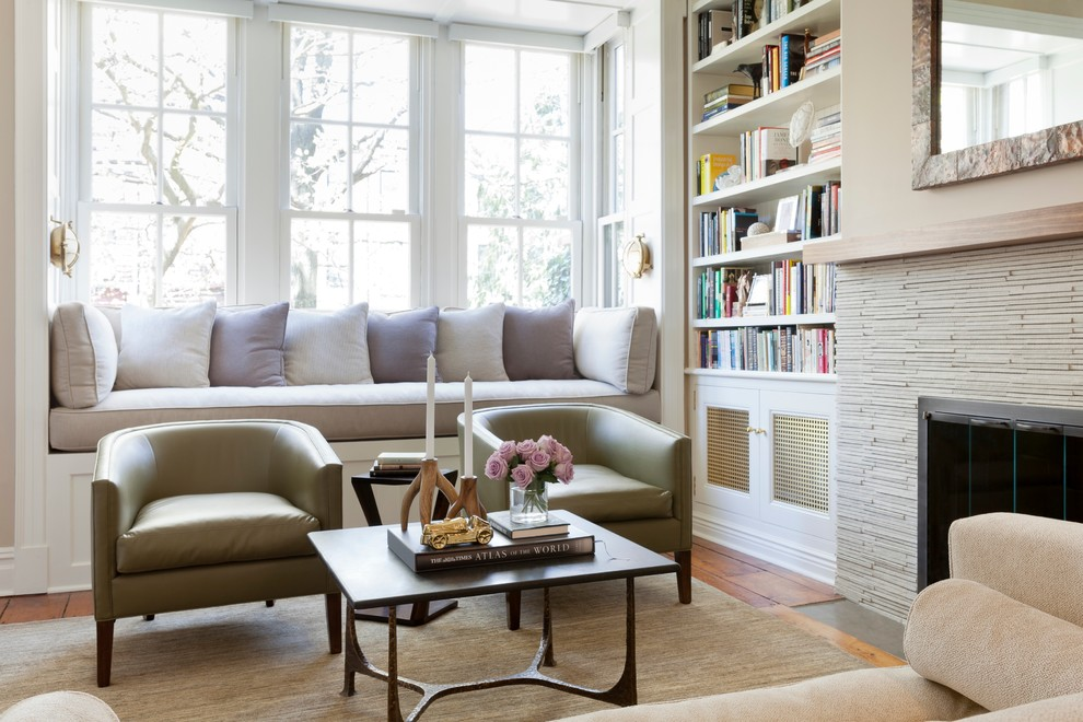 Trendy medium tone wood floor family room library photo in New York with beige walls, a standard fireplace and a stone fireplace