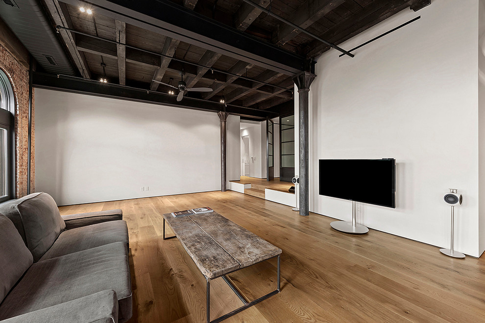 Urban open concept light wood floor family room photo in New York with white walls, no fireplace and a tv stand