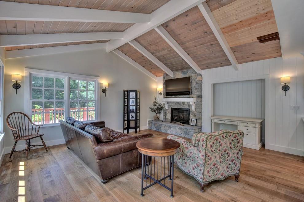 Modelo de sala de estar abierta, de estilo de casa de campo, de tamaño medio, con paredes beige, suelo de madera en tonos medios, todas las chimeneas y marco de chimenea de piedra
