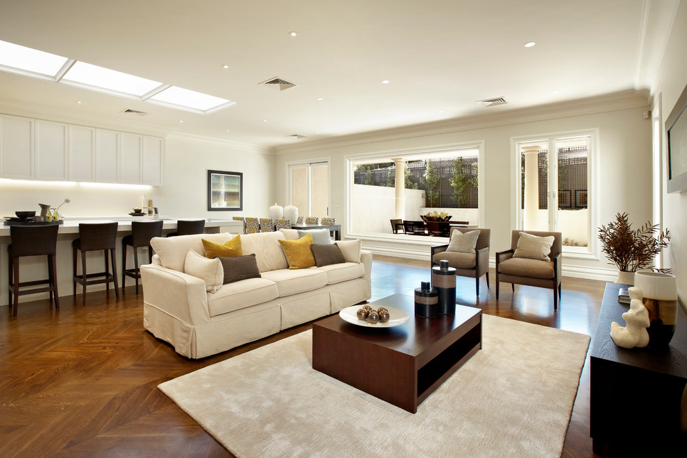Family room - large traditional open concept medium tone wood floor family room idea in Melbourne with white walls and no fireplace