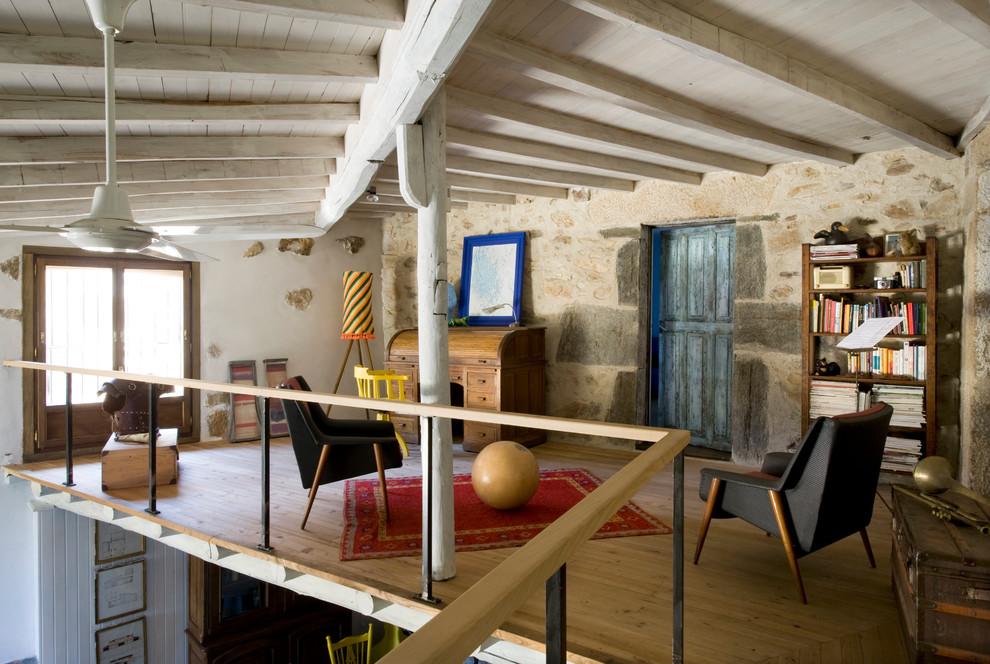 Imagen de sala de estar con biblioteca tipo loft, de estilo de casa de campo, de tamaño medio, sin chimenea y televisor, con paredes marrones y suelo de madera clara