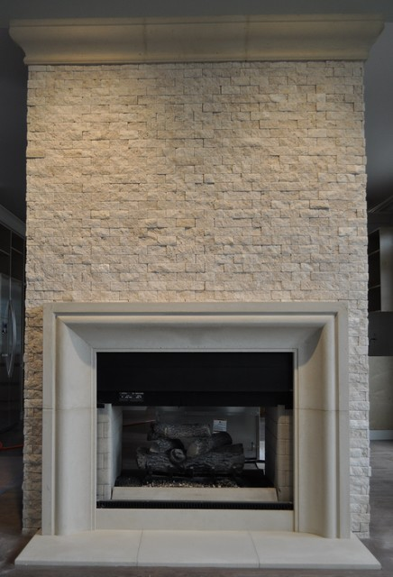 Cast limestone fireplace mantel with custom cast stone crown. Custom cast limestone fireplace surrounds