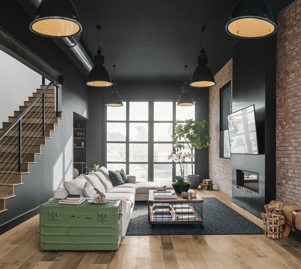 Inspiration for a large industrial open concept medium tone wood floor and brown floor family room remodel with black walls, a ribbon fireplace, a metal fireplace and a wall-mounted tv
