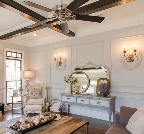 Living room with white paneled walls and french sconces
