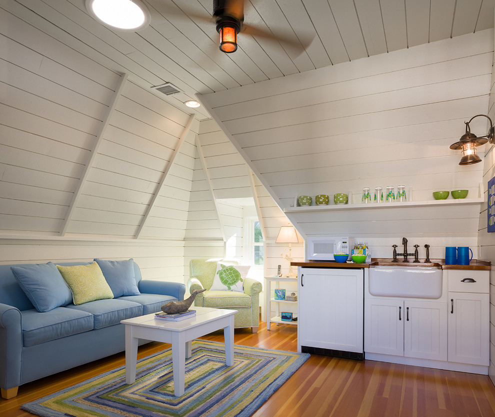 Inspiration for a coastal medium tone wood floor family room remodel in Providence with white walls