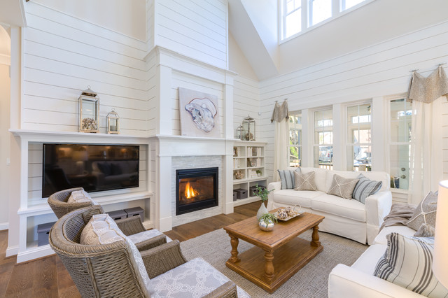 Coastal enclosed medium tone wood floor and brown floor family room photo in Other with white walls, a standard fireplace, a stone fireplace and a wall-mounted tv