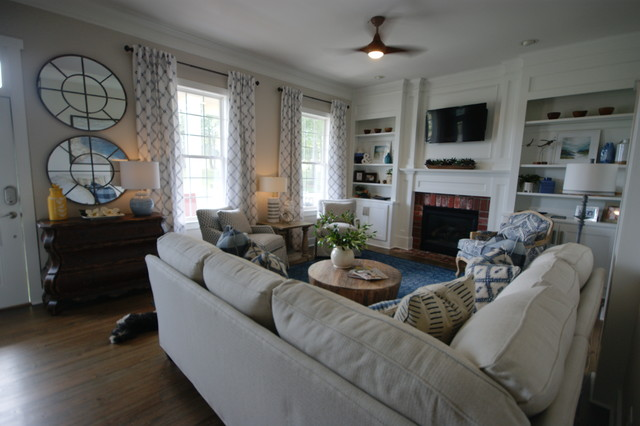 Inspiration for a mid-sized transitional medium tone wood floor family room remodel in Atlanta with gray walls, a standard fireplace, a brick fireplace and a wall-mounted tv