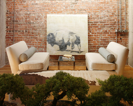A buffalo painting and exposed brick walls contrast nicely with clean upholstery contemporary-family-room