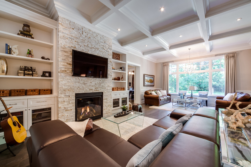 Large elegant open concept medium tone wood floor and brown floor family room photo in Toronto with a stone fireplace, beige walls, a standard fireplace and a wall-mounted tv