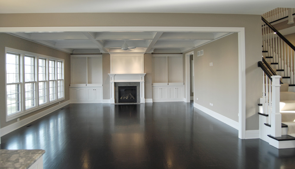 Large elegant open concept dark wood floor family room photo in Chicago with a standard fireplace, a wood fireplace surround, beige walls and no tv