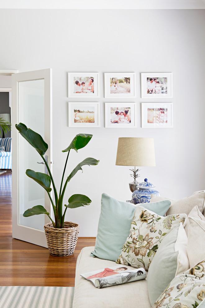 Family room - coastal medium tone wood floor family room idea in Perth with white walls