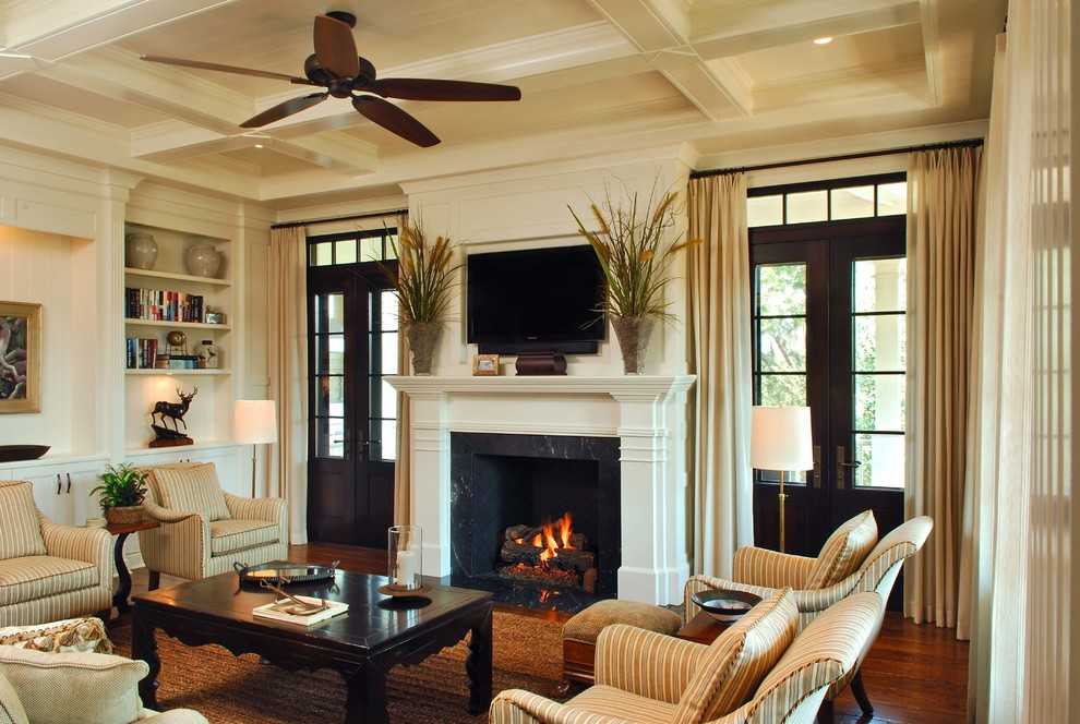 Elegant dark wood floor and brown floor family room photo in Charleston with beige walls, a standard fireplace and a wall-mounted tv
