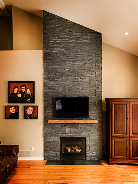 Dark Stone Veneer Fireplace with Wood Mantel traditional family room  Traditional