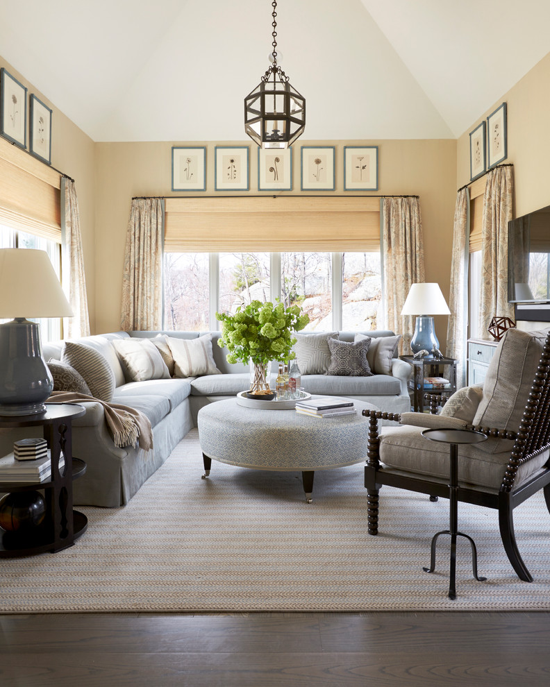 Elegant dark wood floor and brown floor family room photo in Boston with beige walls and a wall-mounted tv