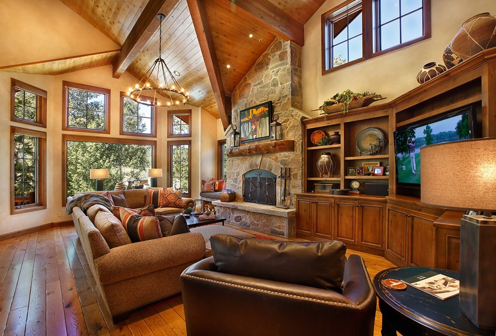 Inspiration for a huge southwestern open concept medium tone wood floor family room remodel in Salt Lake City with a standard fireplace, a stone fireplace, a media wall and yellow walls