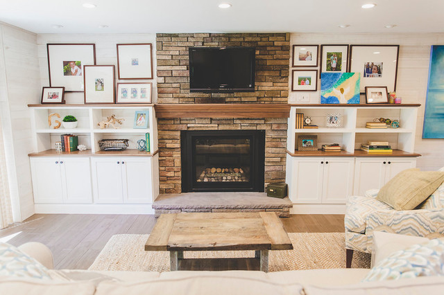 Inspiration for a medium sized beach style open plan family and games room in Providence with a home bar, white walls, porcelain flooring, a standard fireplace, a stone fireplace surround, a wall mounted tv and brown floors.