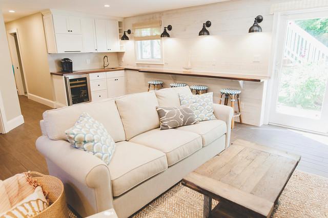 Modelo de sala de estar con barra de bar abierta, marinera, de tamaño medio, con paredes blancas, suelo de baldosas de porcelana, chimenea tradicional, marco de chimenea de piedra, televisor colgado en la pared y suelo marrón