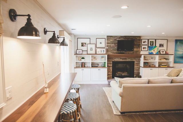 Inspiration for a mid-sized beach style open concept porcelain floor and brown floor family room remodel in Providence with a bar, white walls, a standard fireplace, a stone fireplace and a wall-mounted tv