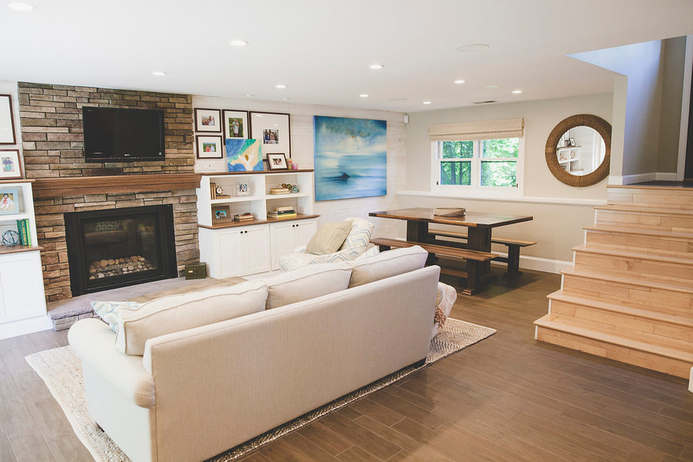 Example of a mid-sized beach style open concept porcelain tile and brown floor family room design in Providence with a bar, white walls, a standard fireplace, a stone fireplace and a wall-mounted tv