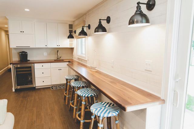 Diseño de sala de estar con barra de bar abierta, marinera, de tamaño medio, con paredes blancas, suelo de baldosas de porcelana, chimenea tradicional, marco de chimenea de piedra, televisor colgado en la pared y suelo marrón