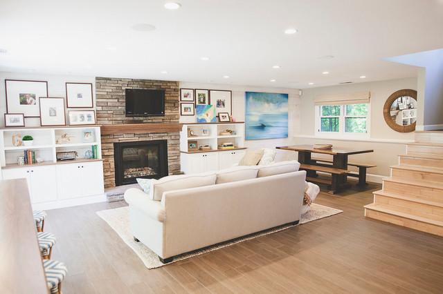 Foto de sala de estar con barra de bar abierta, marinera, de tamaño medio, con paredes blancas, suelo de baldosas de porcelana, chimenea tradicional, marco de chimenea de piedra, televisor colgado en la pared y suelo marrón