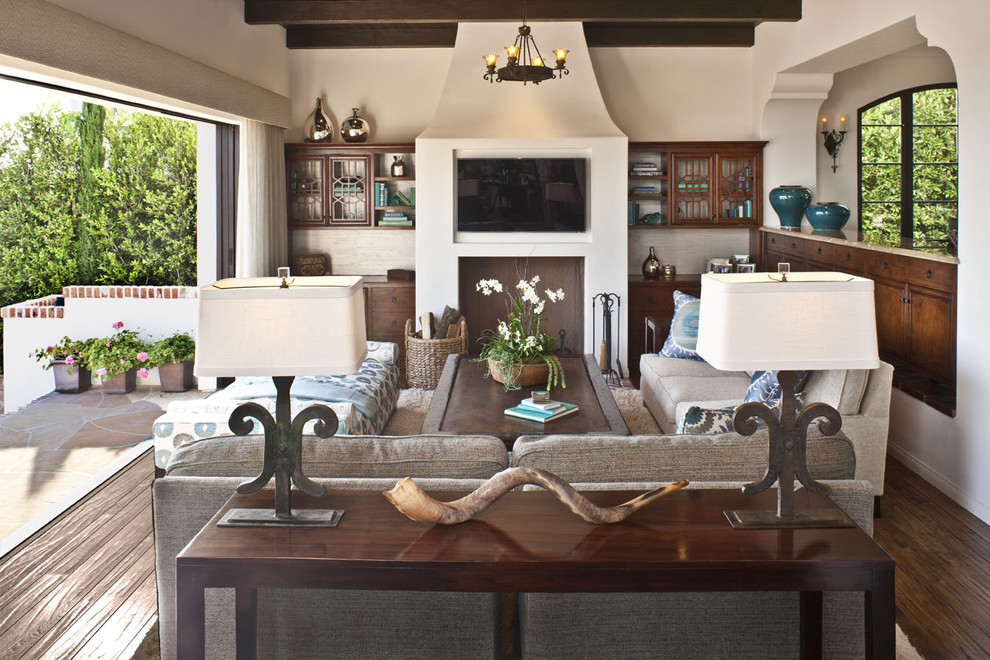 Inspiration for a mid-sized mediterranean open concept dark wood floor and brown floor family room remodel in Los Angeles with beige walls, a wall-mounted tv and no fireplace