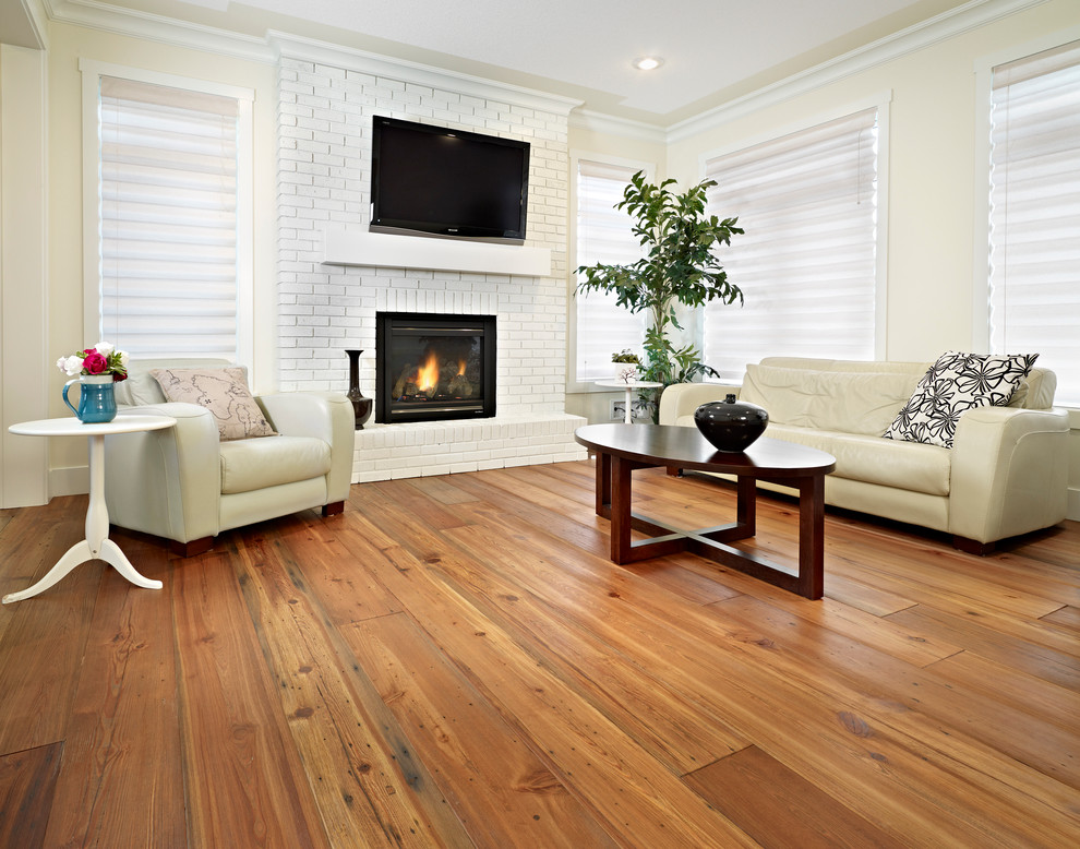 Inspiration for a contemporary medium tone wood floor and brown floor family room remodel in Edmonton with beige walls, a standard fireplace, a brick fireplace and a wall-mounted tv
