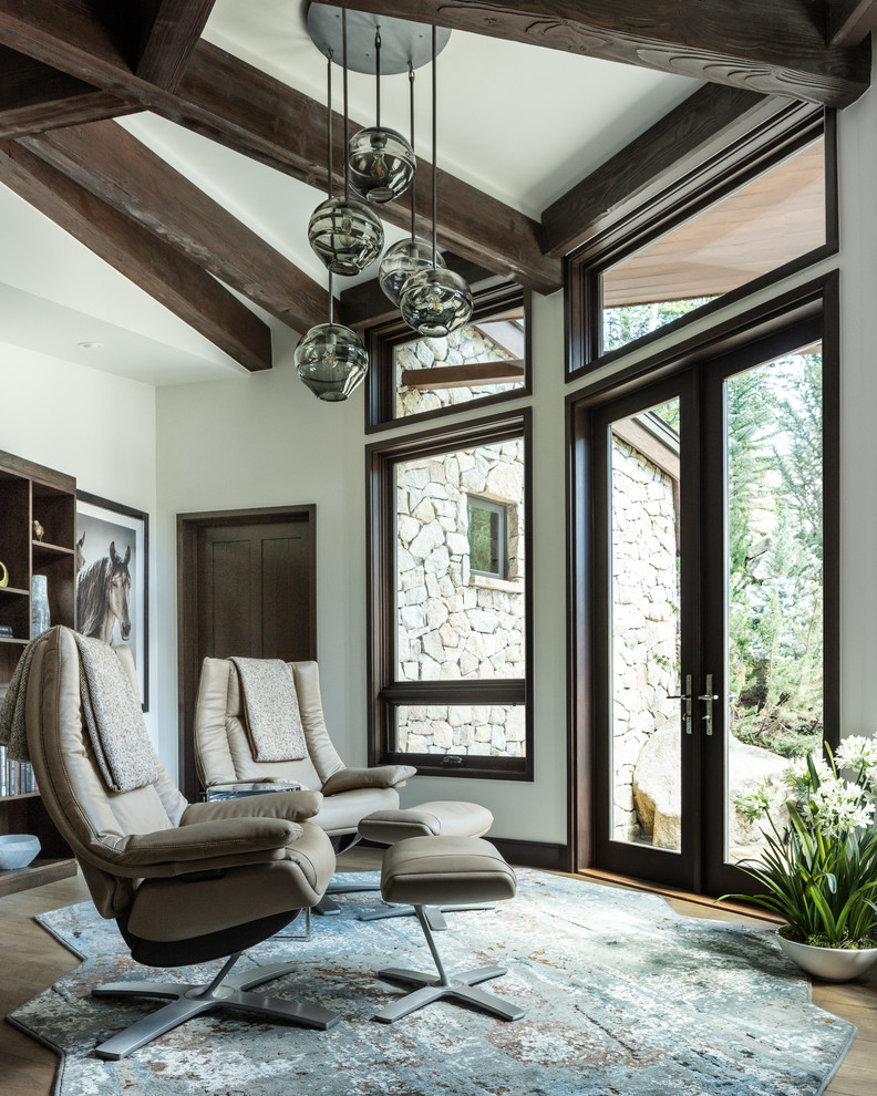 Mountain style light wood floor and beige floor family room photo in Denver with white walls