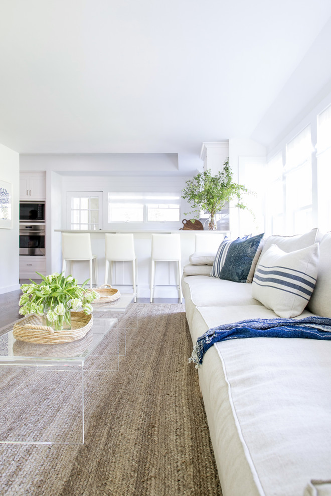 Example of a large beach style open concept family room design in New York with white walls
