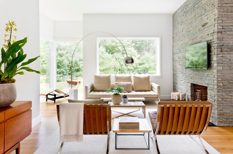 Family room - contemporary open concept medium tone wood floor and beige floor family room idea in New York with white walls, a standard fireplace, a stone fireplace and a wall-mounted tv