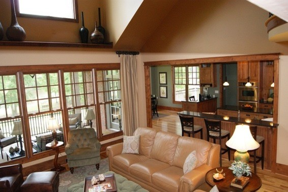 Family room - mid-sized craftsman open concept medium tone wood floor family room idea in Atlanta with beige walls, a standard fireplace, a stone fireplace and a media wall