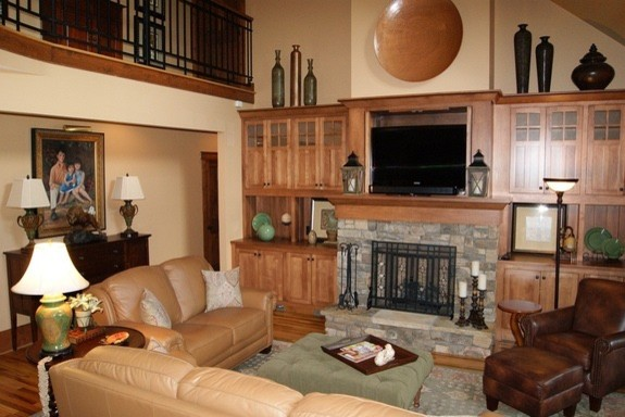 Example of a mid-sized arts and crafts open concept medium tone wood floor family room design in Atlanta with beige walls, a standard fireplace, a stone fireplace and a media wall