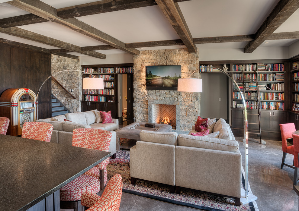 Example of a large mountain style open concept concrete floor family room library design in Other with gray walls, a standard fireplace, a stone fireplace and a wall-mounted tv