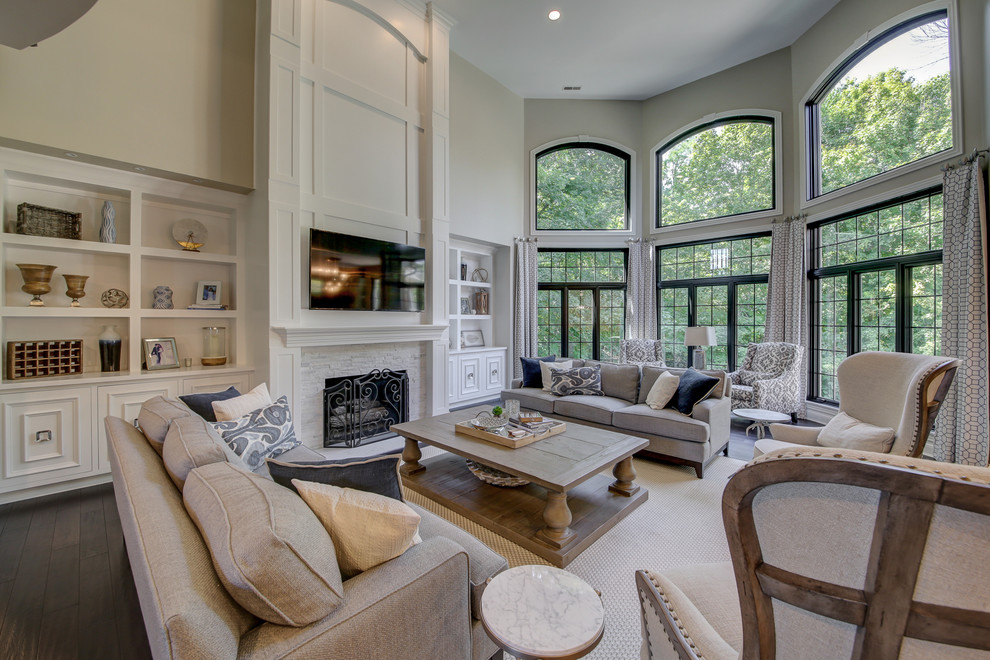 Inspiration for a huge transitional open concept dark wood floor and brown floor family room remodel in Dallas with gray walls, a standard fireplace, a tile fireplace and a wall-mounted tv