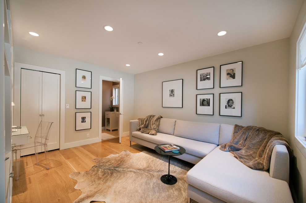 Family room - contemporary enclosed medium tone wood floor family room idea in San Francisco with beige walls
