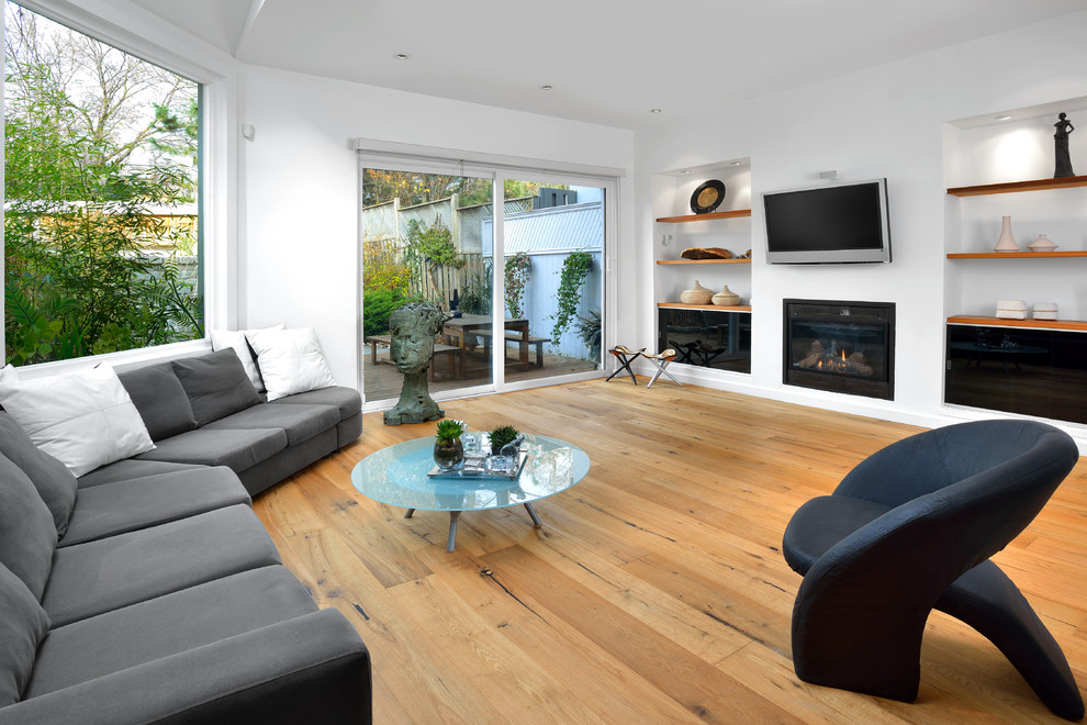 Inspiration for a contemporary open concept light wood floor and beige floor family room remodel in Toronto with white walls, a standard fireplace and a wall-mounted tv