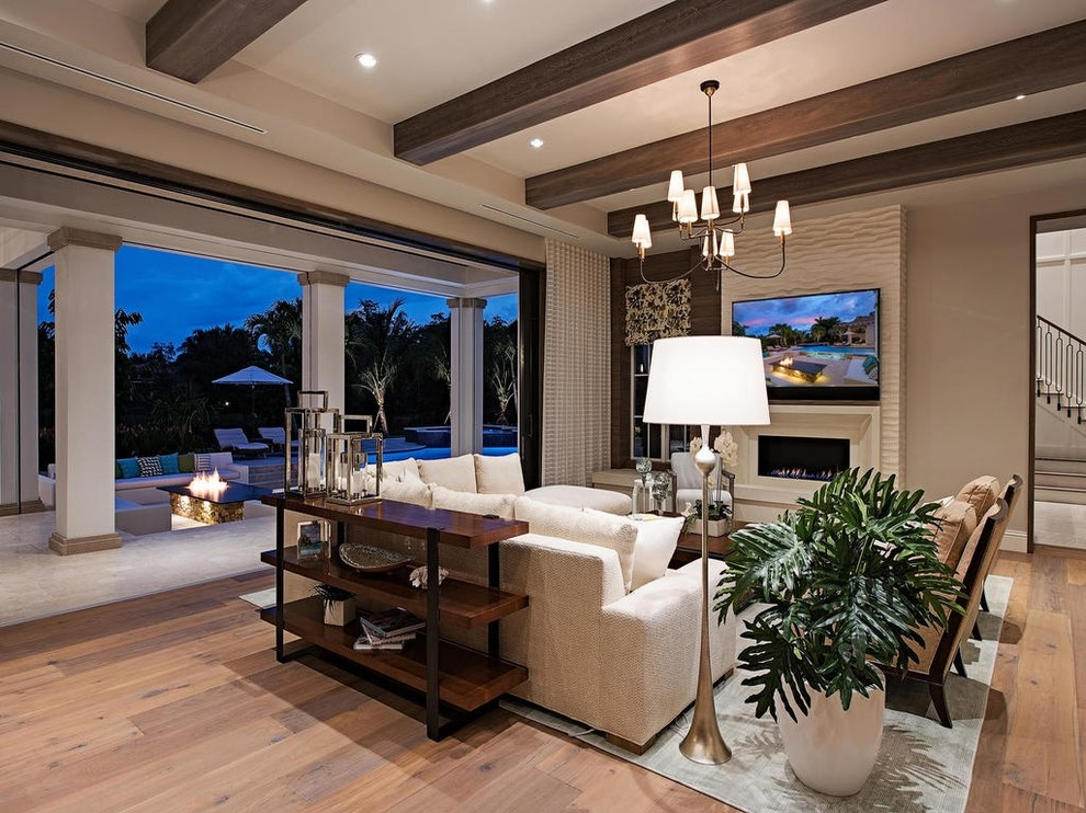 Family room - large transitional open concept medium tone wood floor family room idea in Miami with a wall-mounted tv, beige walls, a tile fireplace and a ribbon fireplace