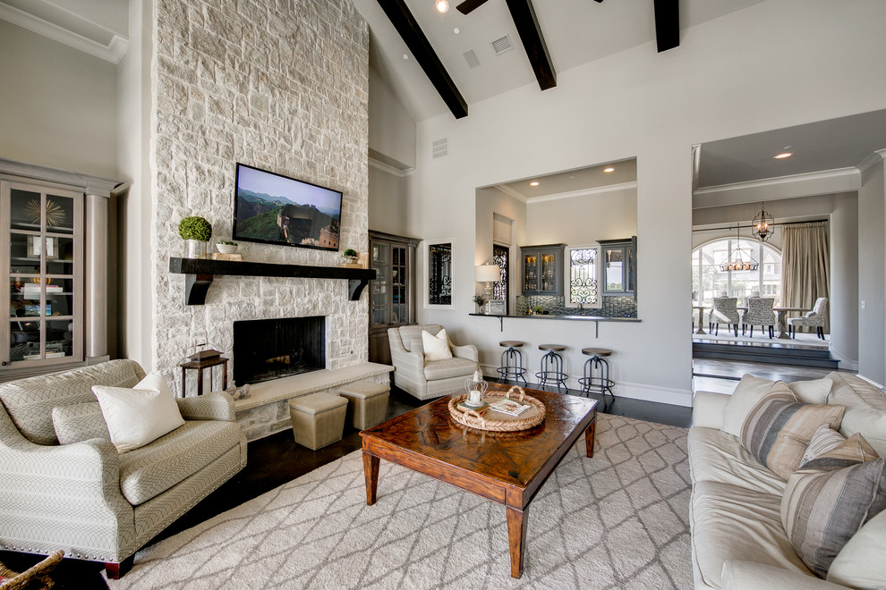 Inspiration for a large coastal open concept dark wood floor family room remodel in Dallas with gray walls, a standard fireplace, a stone fireplace and a wall-mounted tv