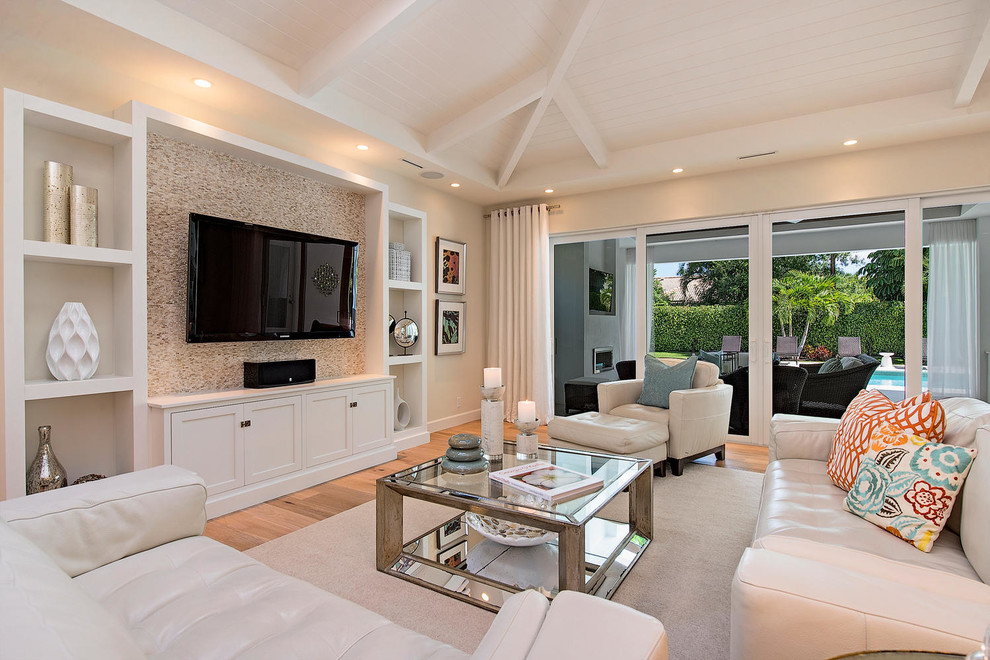 Family room - transitional medium tone wood floor family room idea in Miami with beige walls, no fireplace and a wall-mounted tv