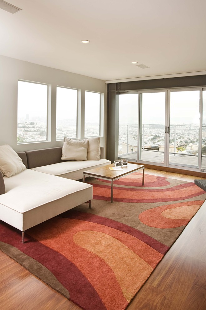 Example of a trendy medium tone wood floor family room design in San Francisco with white walls