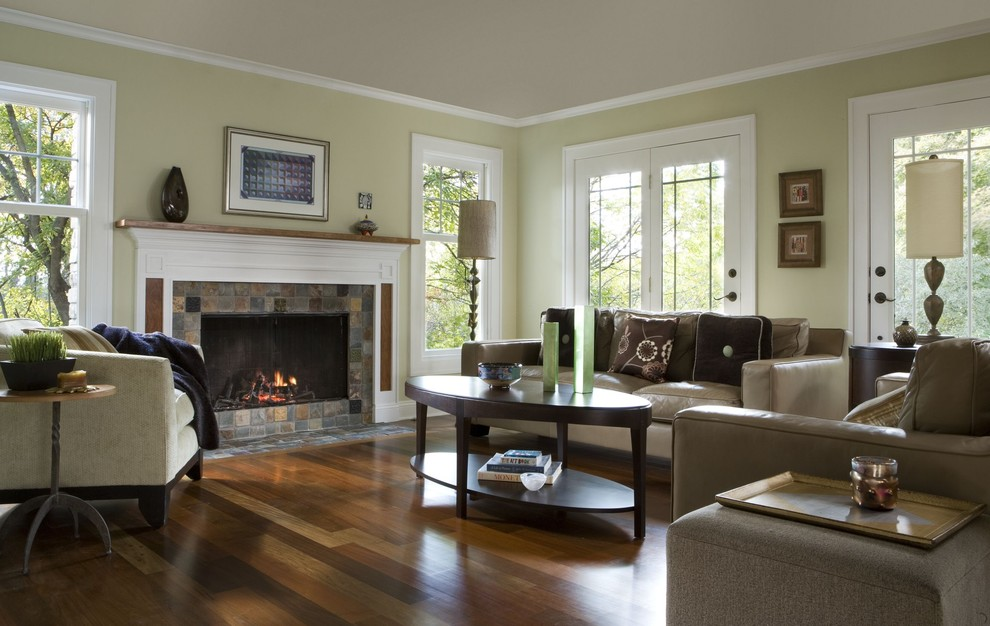 Inspiration for a contemporary medium tone wood floor and brown floor family room remodel in Detroit with beige walls, a standard fireplace and no tv