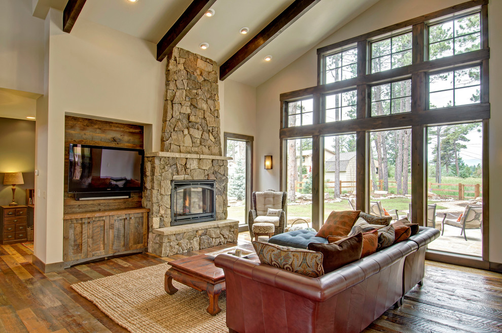 Family room - rustic dark wood floor family room idea in Denver with beige walls, a standard fireplace, a stone fireplace and a wall-mounted tv