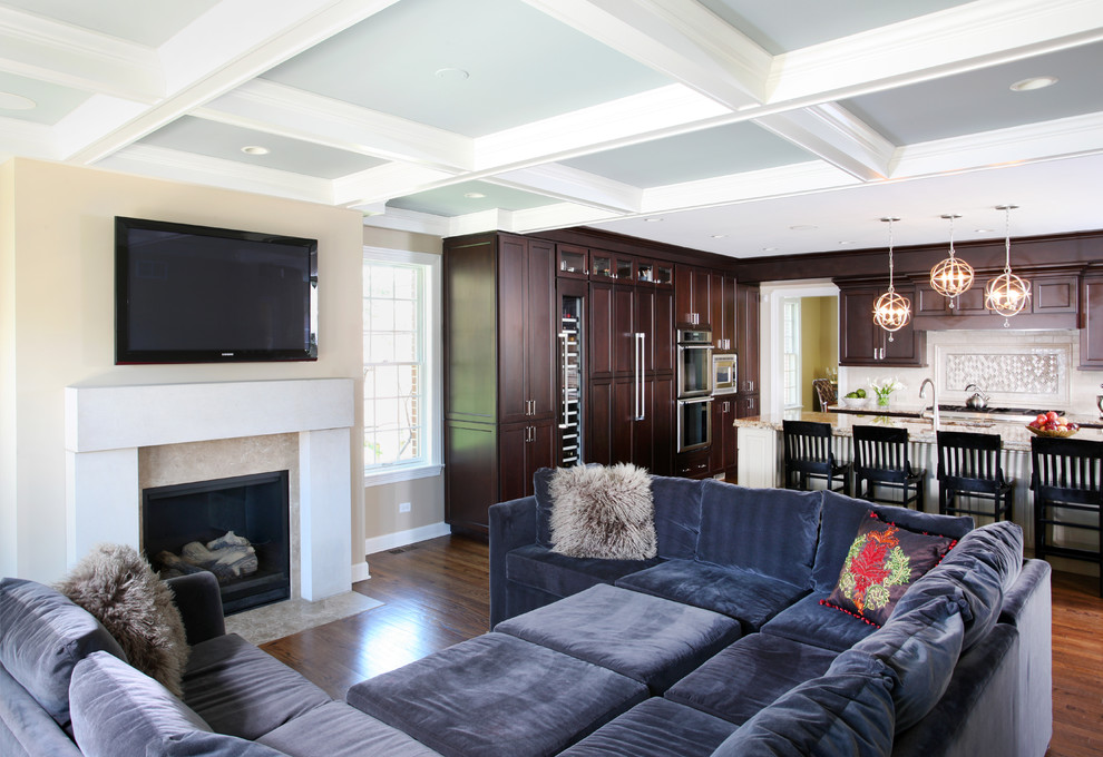 Large elegant open concept dark wood floor family room photo in Chicago with beige walls, a standard fireplace, a wall-mounted tv and a stone fireplace
