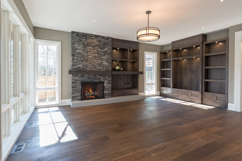 Inspiration for a large contemporary open concept medium tone wood floor family room remodel in Toronto with gray walls, a standard fireplace, a stone fireplace and a media wall