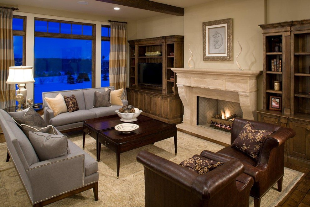 Example of a classic dark wood floor family room design in Minneapolis with beige walls, a standard fireplace and a media wall
