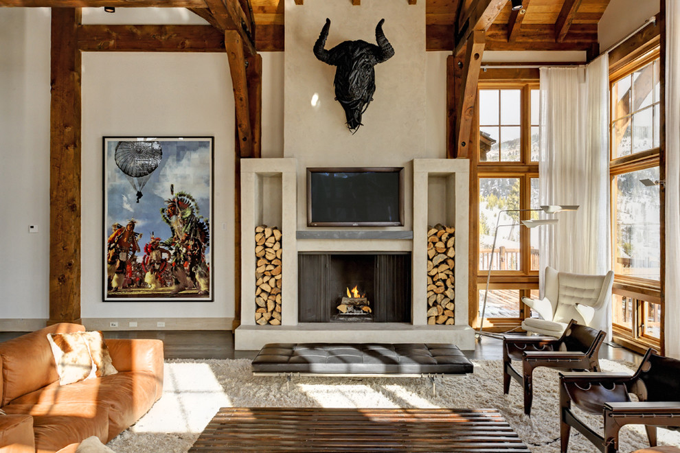 Example of a southwest open concept dark wood floor family room design in New York with beige walls, a standard fireplace and a wall-mounted tv