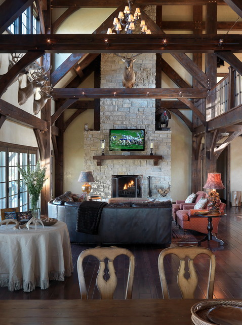 Example of a large mountain style open concept medium tone wood floor family room design in St Louis with beige walls, a standard fireplace, a stone fireplace and a wall-mounted tv